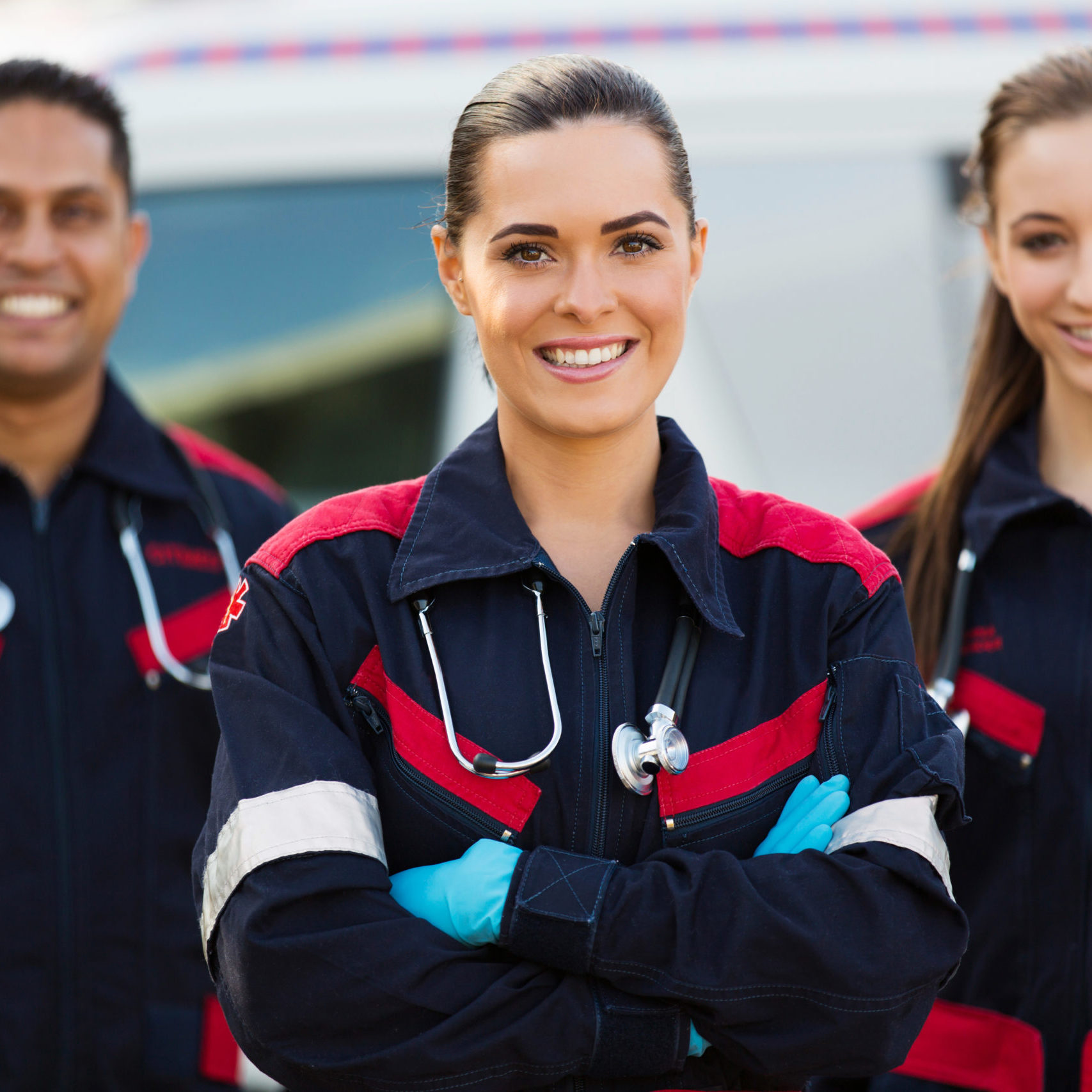 beautiful young EMT and colleagues in front of ambulance